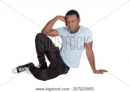 A Young Good Looking African American Man Sitting On The Floor, Resting, With His Hand On His Head,