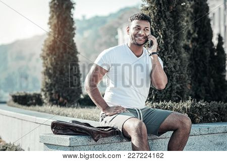 Phone Call. Cheerful Good Looking Handsome Man Putting His Phone To The Ear And Having A Phone Conve