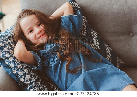cute happy 5 years old child girl relaxing alone at home on cozy couch