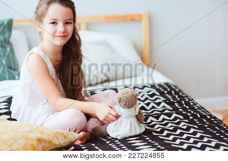 Cute Happy Child Girl Relaxing At Home On The Bed In Her Room In Early Morning. Smiling Kid With Ted