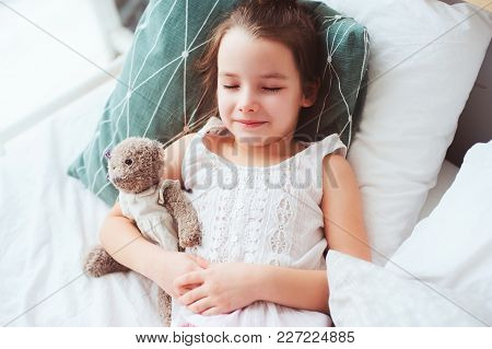 Cute Little Child Girl Sleeping And Watching Sweet Dreams With Her Teddy Bear In Comfortable Bed.