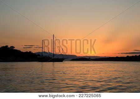 Beautiful Sunset Sailboat Anchoring In A Bay Near Porto Heli, Peloponnese, Greece. Horizontal.