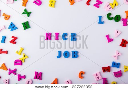 Nice Job. Background Made Of Scattered Colorful Wooden Letters On White Background