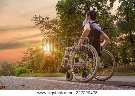 Disabled Or Handicapped Young Man On Wheelchair In Nature At Sun