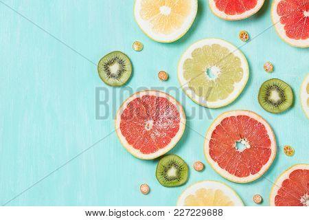 Above View On Thin Citrus Chips: Orange, Lemon, Grapefruit On Turquoise Wooden Background. Vitamins