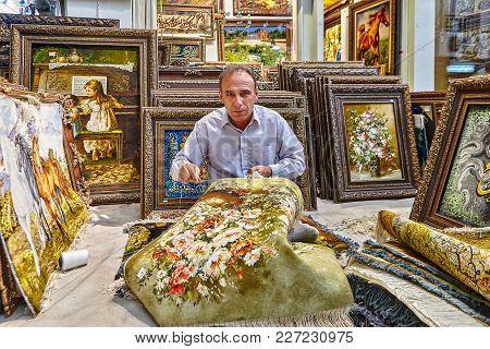 Tehran, Iran - April 29, 2017: A Showroom Of Oriental Rugs  On The Grand Bazaar Of Tehran, A Man Wea