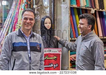 Tehran, Iran - April 29, 2017: Iranian Fabric Sellers Joke About The Female Dummy In A Black Religio