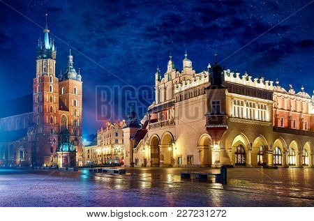 Saint Mary's Basilica in Krakow Poland with Cloth Hall at main square stone paving stones picturesque landscape nighttime city blue sky and stars.