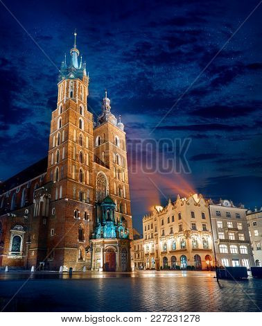 Saint Mary's Basilica famous landmark on market square in Krakow Poland picturesque landscape blue hour with street lamp.