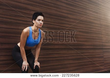 Tired Runner Breathing, Taking Run Break, Leaning At Wooden Wall. Athlete Woman With Hands On Knees