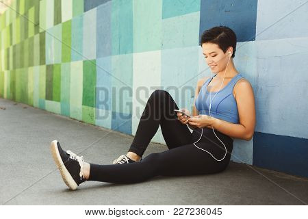 Woman Choose Music To Listen In Her Mobile Phone During Workout In City, Having Rest, Sitting On Flo