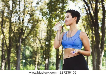 Young Woman Runner Is Having Break, Drinking Water While Jogging In Park, Copy Space
