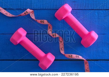 Dumbbells And Tape Measure On Wooden Background. Saturated Colors (blue, Pink). Sport Equipment. Act