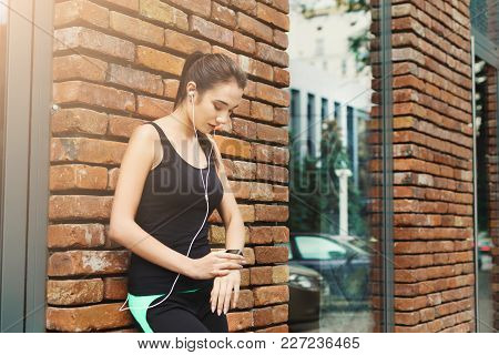 Young Sporty Woman Using Smart Watch, Listening To Music, Standing At Brick Wall Background, Copy Sp
