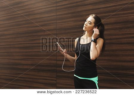 Woman Choose Music To Listen In Her Mobile Phone During Workout In City, Having Rest At Wooden Wall,