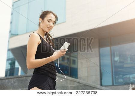 Woman Choose Music To Listen In Her Mobile Phone During Workout In City, Having Rest, Copy Space