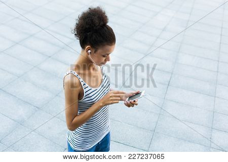 Woman Choose Music To Listen In Her Mobile Phone During Jogging In City, Copy Space