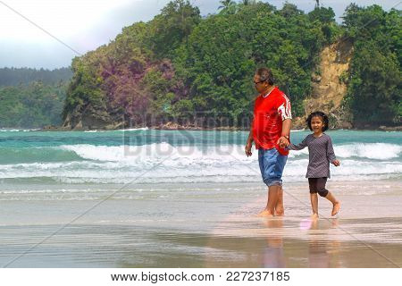 Kudat,sabah-feb 3,2018:father And Kid Holding Hands Together Having Fun And Walking On Tropical Beac