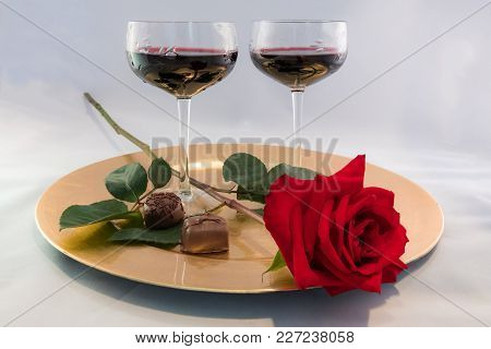 A Still Life Of A Long Stemmed Red Rose Chocolates Abd Two Glasses Of Wine.