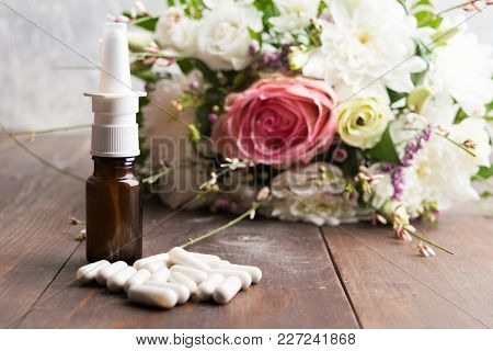 Allergy Concept With Spray And Pills Against Pollen Disease Over Wooden Table