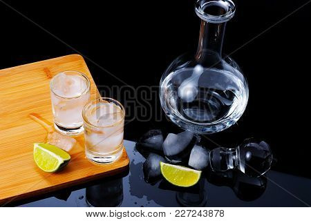 Two Shots With Strong Alcohol On A Wooden Board With Ice Cubes Inside. Next Is The Glass Carafe, Lay