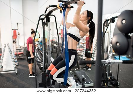 Side View Of Young Woman Exercising On Machines In Modern Gym, Copy Space