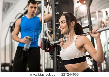 Portrait Of Beautiful Young Woman Smiling Happily While  Training With Barbell In Modern Gym, Copy S