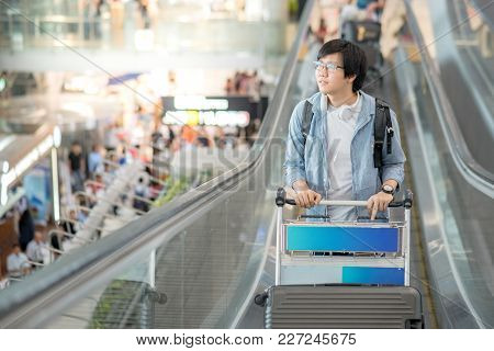 Young Asian Man With Airport Trolley On Escalator, Walking To Check-in Counter In The International