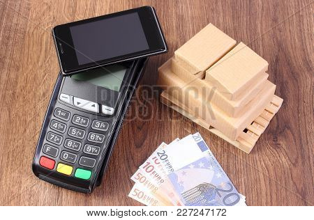 Payment Terminal With Mobile Phone With Nfc Technology, Currencies Euro And Small Wrapped Boxes On W