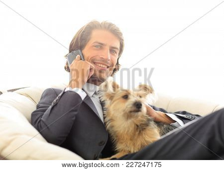 close-up of a businessman talking on the phone and holding his pet.