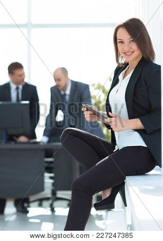 business woman with tablet computer in the background of the office
