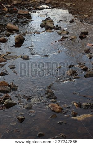 Water Rippling Down A Shallow Creek Or Stream, With Rocks Jutting Out Of The Water, Sky Reflected On