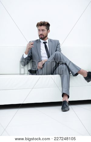 Portrait of a businessman in a suit with a cigarette