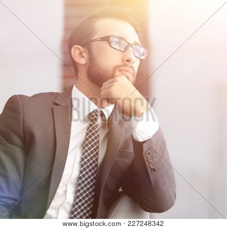 handsome businessman thinks, sitting on couch in his office