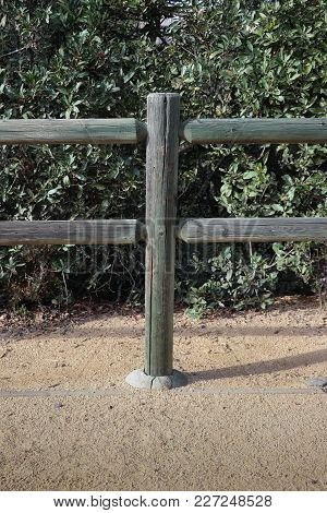 Close Up Of One Wooden Post Set In Concrete In A Two Rail Lodge Pole Fence. The Wood Was Green Treat