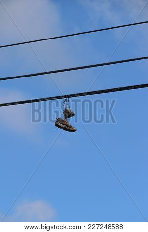 Pair Of Sneakers, Tied Together By Laces, Thrown Over Utility Lines High Above Viewer, Against Blue