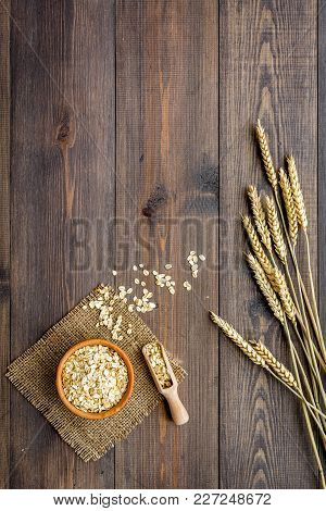 Cereals Concept. Oatmeal In Bowl Near Sprigs Of Wheat On Dark Wooden Background Top View.