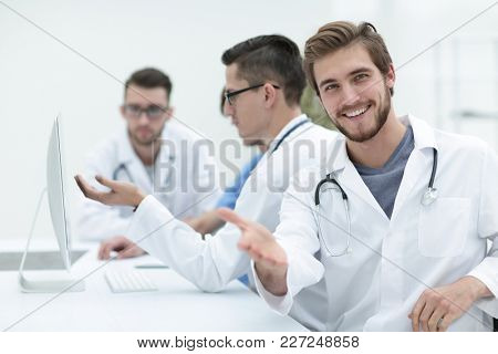 Handsome mature male doctor smiling to the camera