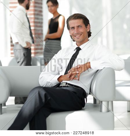 smiling businessman sitting in office chair