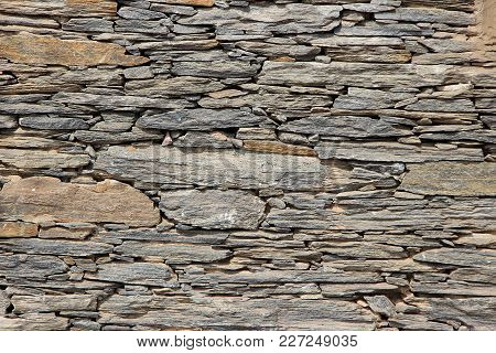 Face Of A Wall With Neatly Packed Up Stone Slabs Of Various Sizes And Shapes