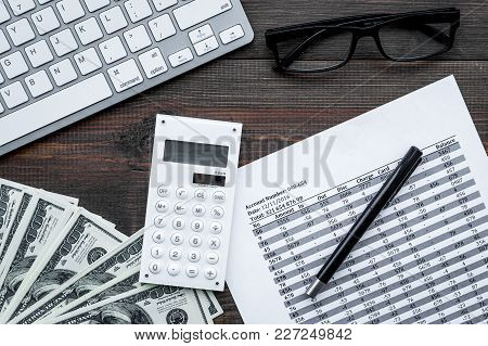 Pay Taxes. Documents Near Calculator, Money, Glasses, Keyboard On Dark Wooden Background Top View.