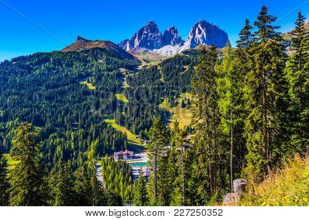 The coniferous forests at the foot of limestone rocks. The most beautiful route in the Italian Dolomites. The concept of active and car tourism