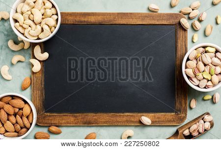 Assortment Of Nuts, Cashew, Pistachio Almond Healthy Snack. Chalkboard With Copy Space, Top View