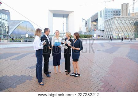 Employees Of Business Of Business Organization Working Outside, Talking By Smartphone And Discussing
