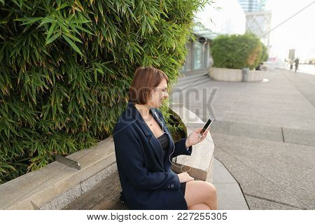 Businesswoman Listening To Music And Chatting With Smartphone And In Ear Phones Outside. Concept Of