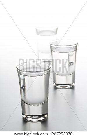 German Hard Liquor Korn Schnapps In Shot Glasses Over White Background
