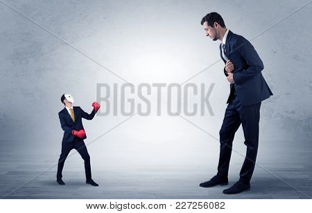 Big businessman being afraid of small masked businessman with box gloves in an empty room concept