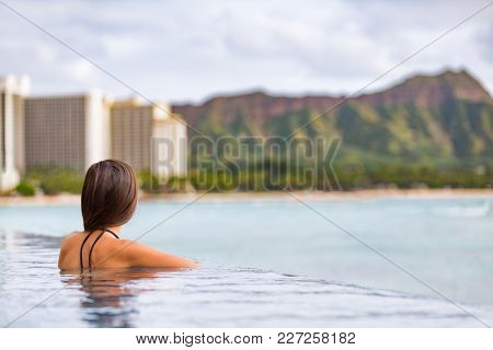 Hawaii vacation Honolulu travel tourist woman relaxing in swimming infinity pool at luxury resort hotel in Waikiki beach, watching sunset. Girl on USA summer travel landscape banner panoramic.