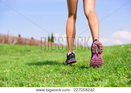 Running girl runner jogging on grass on trail run in summer park . Athlete legs and shoes jumping from behind, heels and calves,