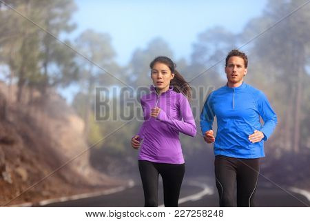 Runners training outside running on road - Two athletes couple jogging in nature wearing sportswear clothing for cold morning fog weather - autumn exercise. Sports lifestyle.